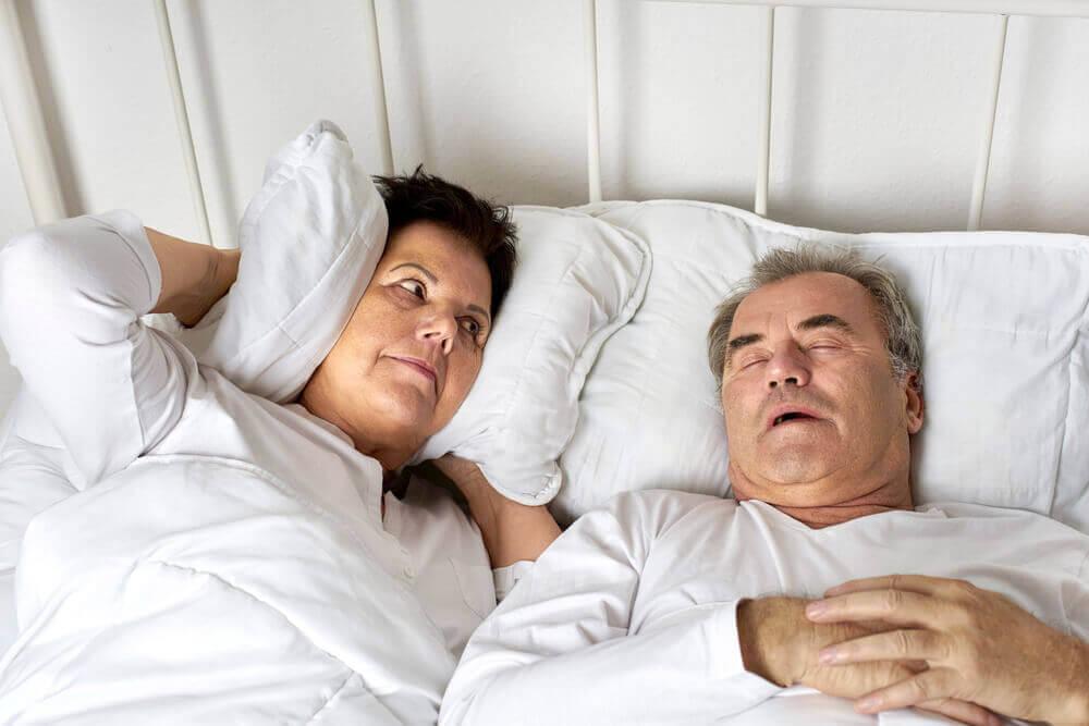 Un homme qui ronfle au lit.