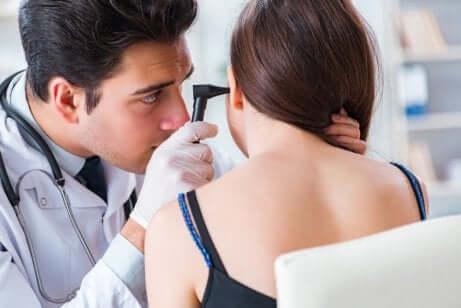 Un médecin en pleine stimulation du nerf vague dans l'oreille d'une patiente.