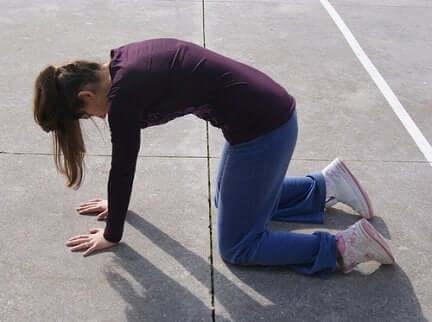 Une femme réalise un exercice sur le sol.