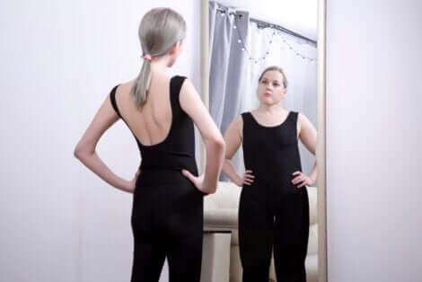 Une jeune femme devant un miroir avec une image erronée.