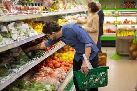 Un homme achetant des légumes au supermarché.