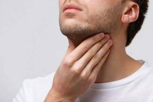 Un homme qui a mal aux cordes vocales.