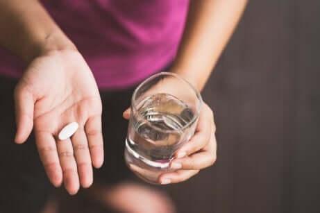 Un comprimé de paracétamol dans une main avec un verre d'eau.