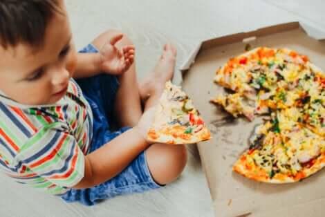 Un enfant qui mange de la nourriture rapide.
