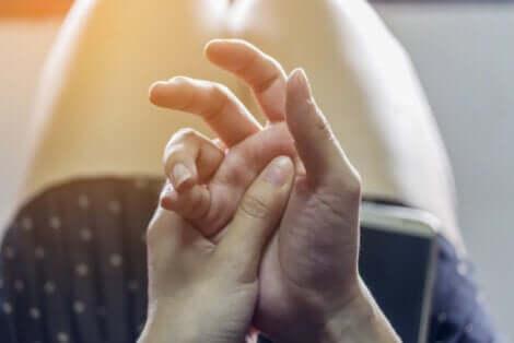 Une personne qui se touche les mains.