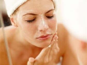 Une femme nettoie son visage.