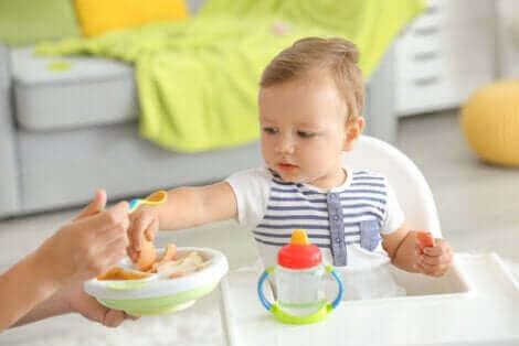 Un bébé mangeant avec une cuillère.