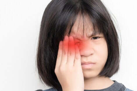 Une jeune fille qui a mal à un oeil.
