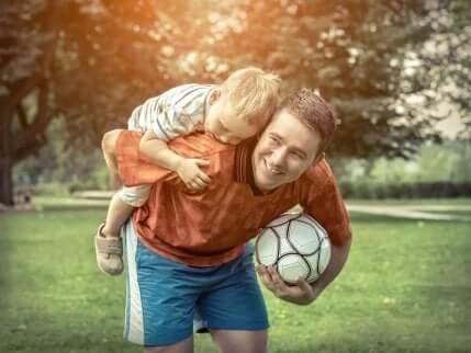 Un adulte qui joue au ballon avec un enfant.