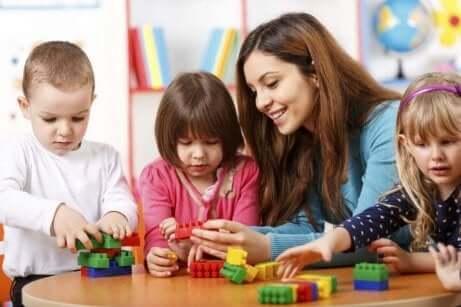 Enfants qui jouent autour d'une table avec une adulte.