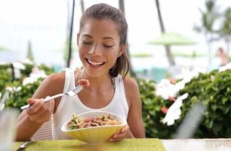 Une jeune femme qui mange une salade avec du thon.