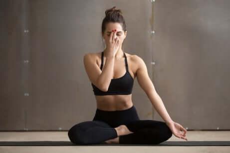 Une femme qui fait l'exercice de yoga du souffle de la lune.
