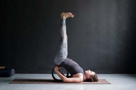 Une femme dans la posture de yoga des jambes contre le mur.