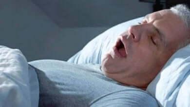 Un homme qui dort la bouche ouverte.