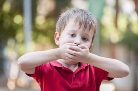 Un enfant qui se couvre la bouche.