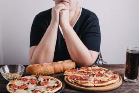 Une femme anxieuse devant deux pizzas et un coca cola.