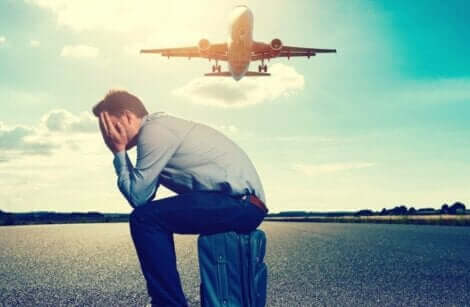 Un homme assis sur sa valise devant un avion qui décolle.