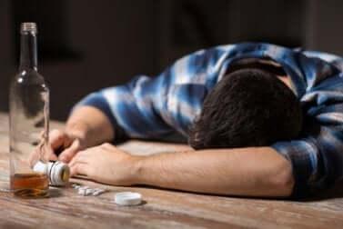 Un homme endormi sur une table qui a bu une bouteille d'alcool entière.