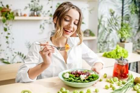 Une femme qui mange une salade en souriant.