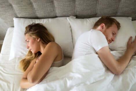 Un couple qui se tourne le dos dans un lit.
