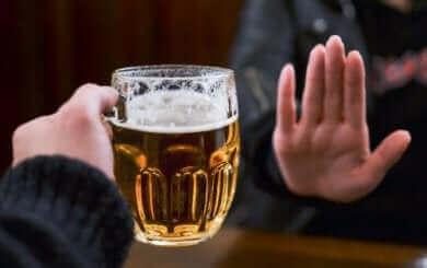 Une main qui dit non à un verre de bière.