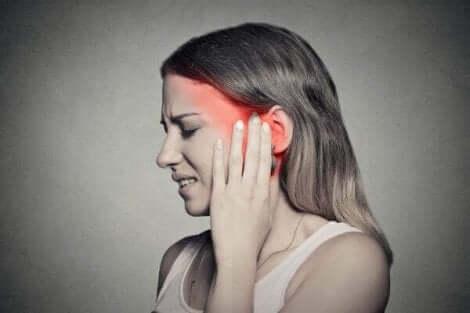 Une femme qui ressent une douleur à l'oreille.