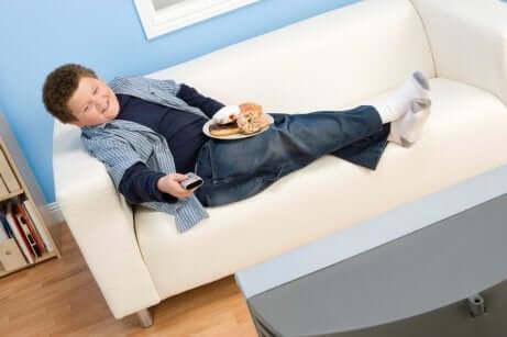 Un enfant devant la télévision qui mange des sucreries.