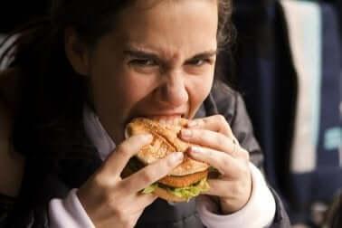 Une femme qui mange un hamburger.