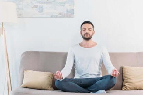 Un homme qui médite dans son salon.
