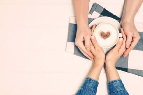 Les mains d'un couple autour d'une tasse de café.