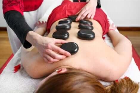 Massage aux pierres chaudes sur le dos d'une femme.