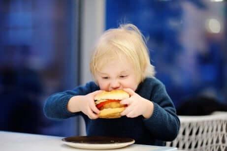 Un enfant qui mange un hamburger.