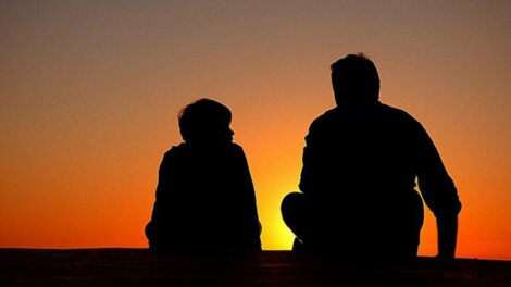 Un père et son fils devant un coucher de soleil.