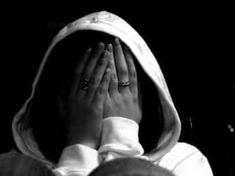 Une personne anxieuse qui se cache derrière ses mains.