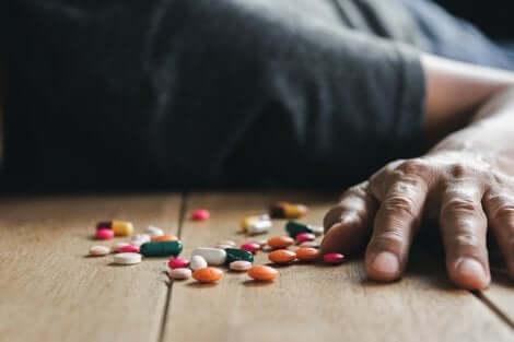 Une personne allongée avec des médicaments par terre.
