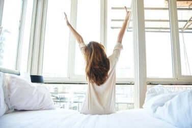 Une femme qui s'étire en se levant du lit.