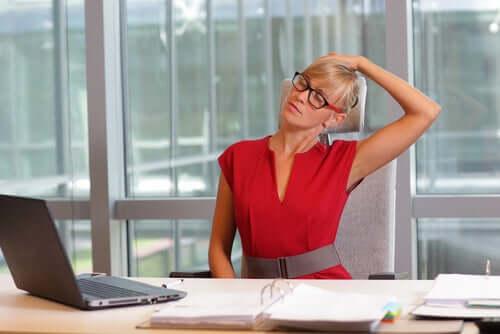 Une femme qui s'étire au travail devant son bureau.