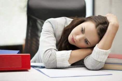 Une femme qui se repose sur son bureau.