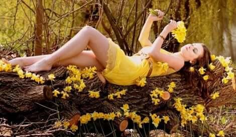Une jeune femme allongée dans la nature avec des fleurs jaunes.