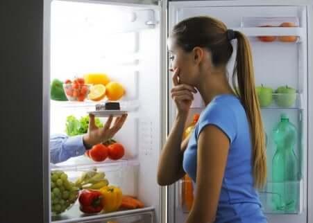 Une femme devant un frigo ouvert qui hésite entre un fruit et une part de gâteau au chocolat.