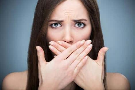 Une femme qui se cache la bouche avec les deux mains.
