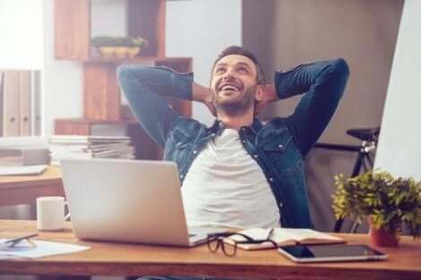 Un homme souriant à son bureau.