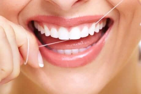 Une femme qui se passe le fil dentaire.