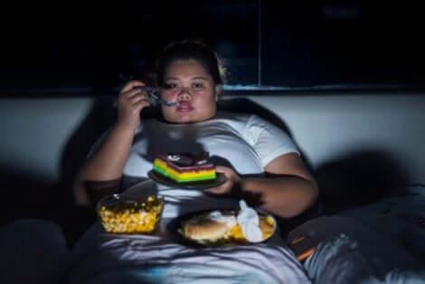 Une femme obèse qui mange des pâtisseries devant la télé.