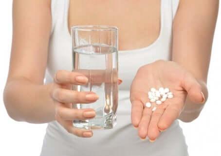 Pastilles de médicaments dans une main avec un verre d'eau.