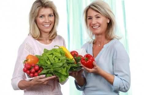 Deux femmes avec des légumes dans les mains.
