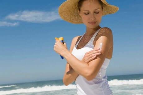 Une femme qui applique une protection solaire.