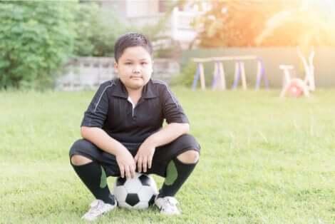 Un enfant assis sur un ballon en tenue de football.