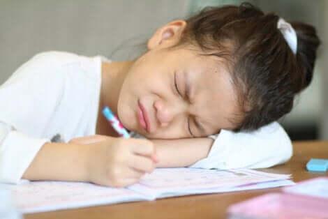 Une jeune fille fâchée devant ses devoirs.