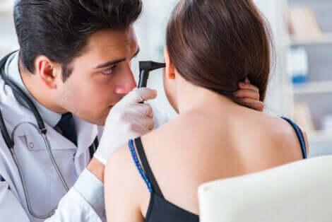 Un médecin qui examine les oreilles d'une femme.